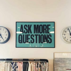 A wall poster that says 'ask more questions'