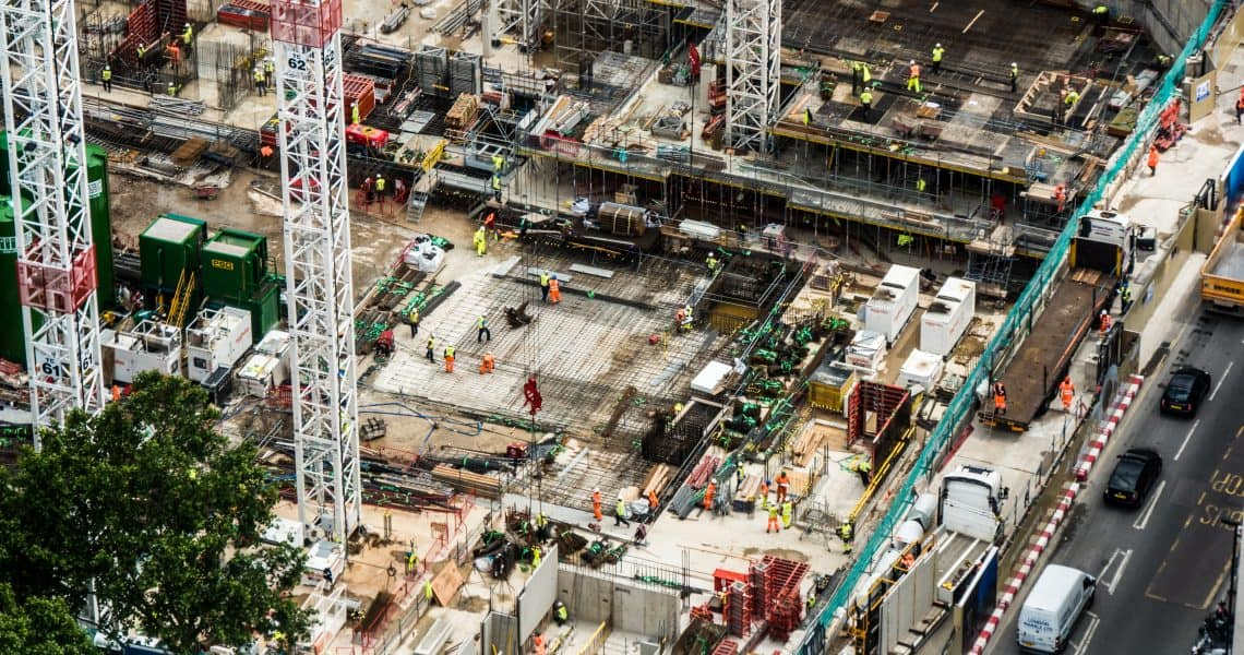 An ariel view of a chaotic London construction site with traffic flowing past it