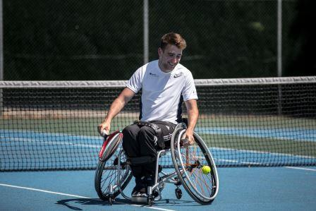 A man smiling while playing wheelchair tennis after playing a point. He is outside on a blue hard court with the net in the background.