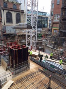 Photograph taken during an inclusive design site visit. The image shows a construction site for a new central london hotel. In the foreground there are steel latices on the floor metal pipes being lowered by crane. In the background, workers move planks of wood and survey the scene
