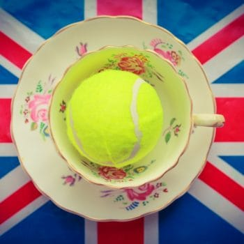 A cup and saucer with a yellow tennis ball inside, on top of a union jack flag